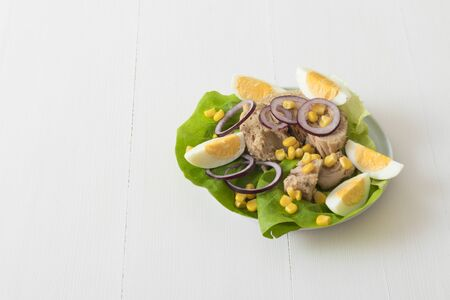 Canned tuna with eggs, suggar corn, red onion rings on green lettuce leaf, slice of lemon in pocelain bowl. Tuna fish salad. White wooden table background. Free space for your text. Фото со стока