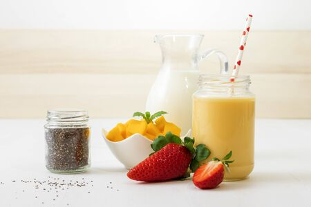 Glass of fresh mango smoothie or mango milkshake with milk in glass pitcher, pieces of mango in porcelain bowl and few real fresh strawberries on white wooden table. Closeup view.