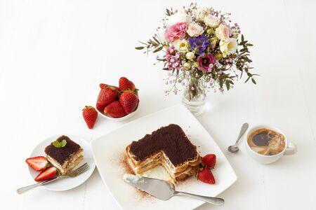 Tiramisu, homemade Italian sweet no bake cheesecake dessert, on white plate embellished with fresh mint and a few real strawberries, cup of coffee, bowl with strawberries and flowers on white table. 版權商用圖片