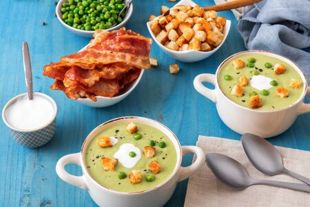 Blue wooden table with bowls of thick green pea soup embellished with roasted rusks, green peas, slices of grilled bacon, crushed black pepper and cream.