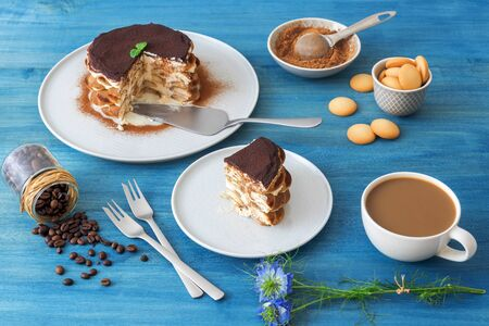Round tiramisu, homemade no-bake traditional Italian sweet dessert. Blue table with cake, bowl with cocoa powder, round sponge biscuits, coffee beans and coffee with milk. Blue background with flowers.