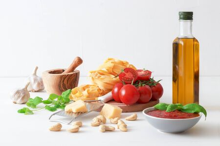 Table with ingredients to make tomato pesto. Tomatoes, garlic, fresh oregano and basil herbs, bottle of olive oil, few cashew nuts, parmesan cheese, cheese grater, wooden mortar and homemade pasta. Dark blue background.