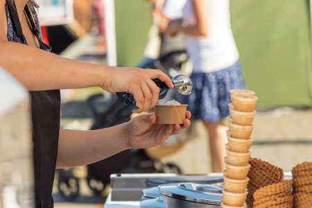 Female vendor sells ice cream at Naplavka farmers street food market in Prague, Czech Republic.