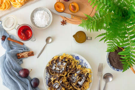 Sweet pasta dessert, noodles with poppy seeds, plum compote from fresh plums, dark background, white wooden table decorated with fresh flowers. Dry whole poppy plant in background. Stok Fotoğraf