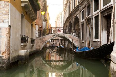 Narrow canal with gondolas in Venice, Italy  photo