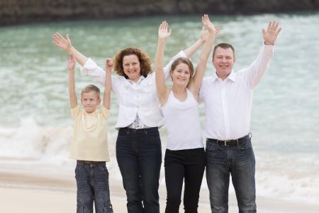 mujer hijos: Familia en una playa para levantar los brazos en el aire Foto de archivo
