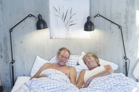 Senior couple sleeping in bed photo