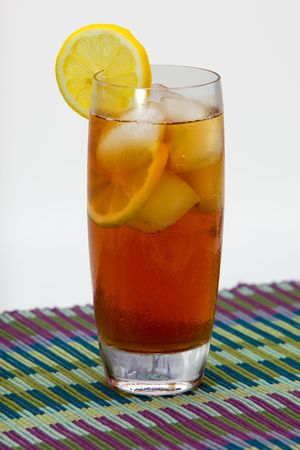 Iced tea with slices of lemon on place mat.