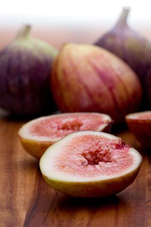 Whole and sliced fresh figs on wooden board.