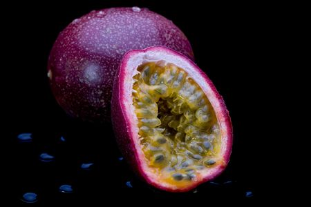 Whole and sliced passion fruit on black background with water droplets.