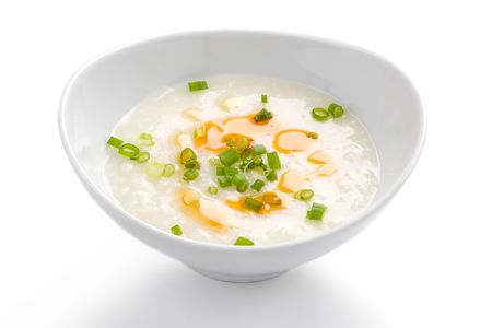 chicken rice: Asian rice porridge in white bowl on white background. Stock Photo