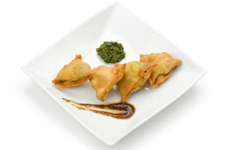 Samosas with mint and tamarind chutney on white square plate.