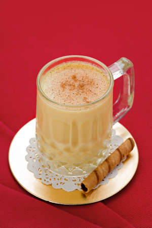 egg nog: Egg nog in glass on gold coaster with cookie on red background. Stock Photo