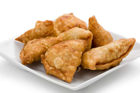 spicy: Several Samosas on a square plate on a white background. Stock Photo