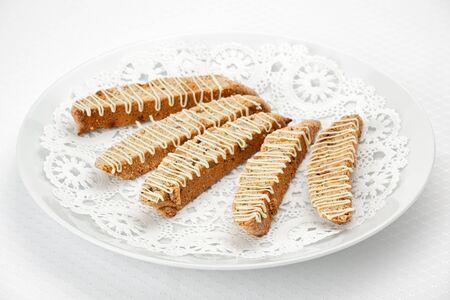 白いプレートにホワイト チョコレートとヘーゼル ナッツ ・ ビスコッティ。 写真素材