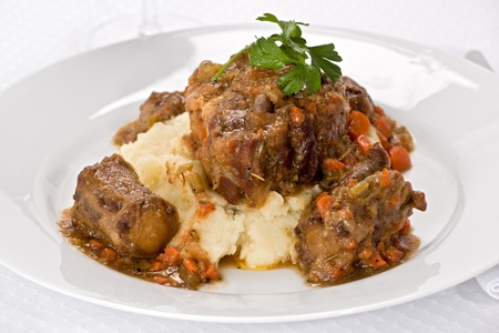 Oxtail stew on mashed potatoes on white plate.
