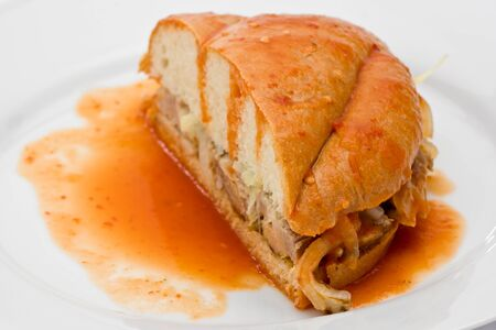 Mexican drowned sandwich with pork on a white plate.