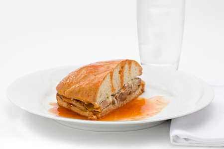Mexican drowned sandwich with pork on a white plate with glass of water. Banco de Imagens
