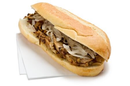 Pork sandwich with pickled onions on napkins.