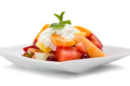 新鮮なプレート フルーツ サラダ ヨーグルトと白い背景にミントを添えています。