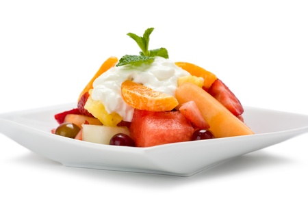 A plate of fresh fruit salad with yogurt and garnished with mint on white background. Stock Photo - 8860610