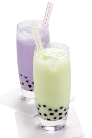 Taro and Honeydew milk tea with tapioca pearls with straws on white background.