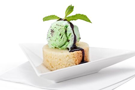 A scoop of mint ice cream on a slice of pound cake with chocolate sauce and garnished with mint.