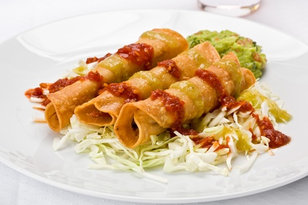 Three taquitos on a bed of sliced cabbage with guacamole, red and green sauce, on a white plate.