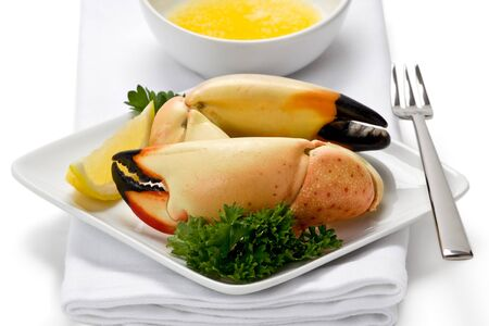 Two florida stone crab claws on appetizer plate with slice of lemon, and a side of melted butter. Stock Photo