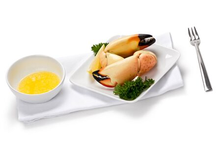 Two florida stone crab claws on appetizer plate with slice of lemon, and a side of melted butter. photo