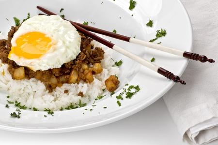 Macanese minced meat dish with potatoes and rice with a fried egg on top.