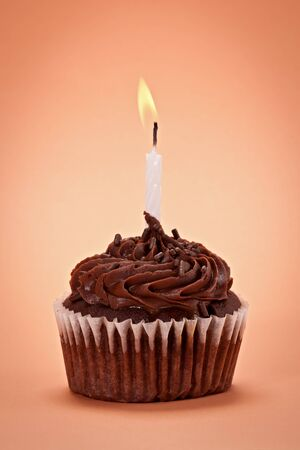 Chocolate cupcake with chocolate sprinkles and white candle on orange background.