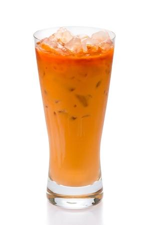 Glass of thai iced tea against light white background. photo