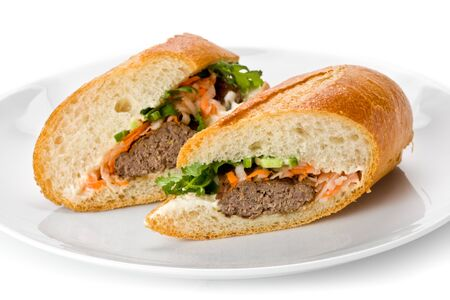 Vietnamese sandwich, or Ban Mi on a white plate on a white background.