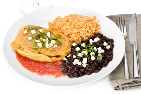 кинза: Cheese chile relleno with black beans and rice garnished with cilantro on white plate.