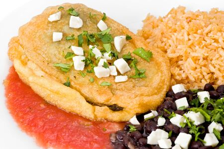 Cheese chile relleno with black beans and rice garnished with cilantro on white plate.