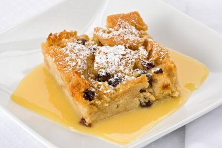 pudding: Bread pudding with bourbon sauce on a square plate with fork.