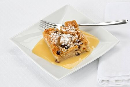 Bread pudding with bourbon sauce on a square plate with fork.
