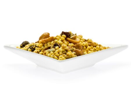 白い前菜皿の上に南部と呼ばれるインドのスナック食品。
