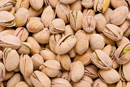 Background texture of salted, and roasted pistachio nuts in their shells.