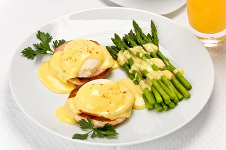 Two poached eggs, and canadian bacon, on an english muffin topped with hollandaise sauce with green asparagus on the side on white plate.