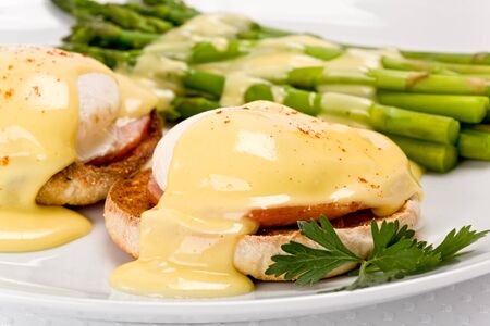 english breakfast: Close up of two poached eggs, and canadian bacon, on an english muffin topped with hollandaise sauce with green asparagus on the side on white plate.