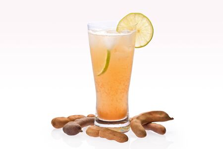Ice cold tamarind drink in glass with slices of lime, and tamarind pods on graduated background.