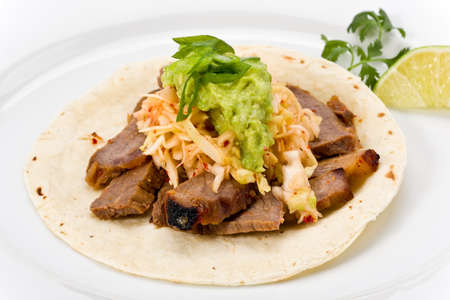 corn tortilla: Korean styled taco with beef, pickled cabbage and guacamole on a corn tortilla.