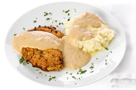 Chicken fried steak with mashed potato and gravy on a white plate.