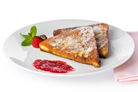 白い皿に、ラズベリー ソース添えのフレンチ トーストの 2 つのスライス。