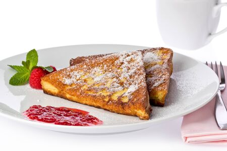 Two slices of french toast with a raspberry sauce on a white plate.