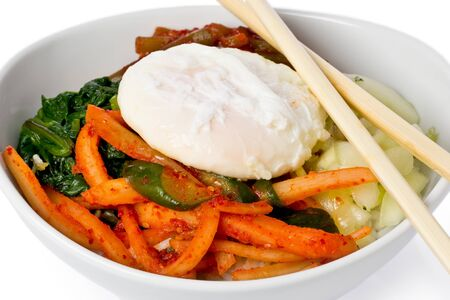 Korean dish with rice, topped with sauteed, and pickled vegetables, korean chili, and an egg.