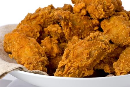 pollo frito: Plato de alas de pollo frito crujiente y baquetas.