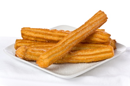 churros: Several churros on small plate against white background.